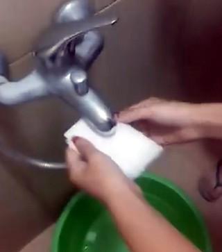 Hình ảnh sinh viên dùng khăn trắng bịt vòi xả nước.