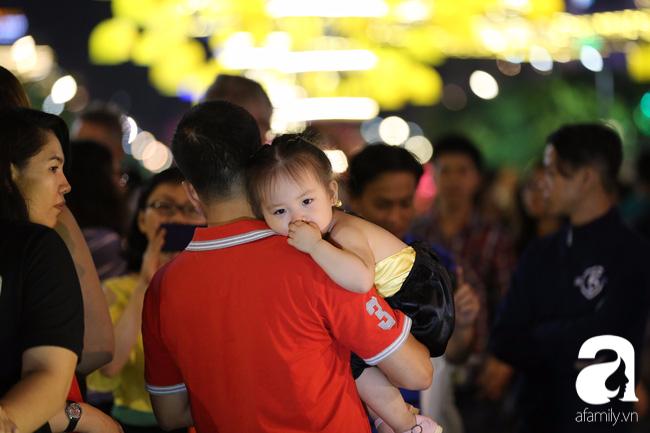 Các bé được ba mẹ cõng trên vai để dễ tham quan.