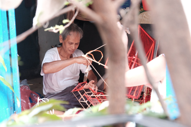 Men theo con đường dẫn vào giáo xứ Phú Bình, chúng tôi tìm đến nhà của chú Hỉ Tạo Sáng (65 tuổi, người gốc Hoa). Tại đây, hai cha con ông Sáng đang cặm cụi dán những miếng giấy lụa màu đỏ rực vào những khung lồng đèn hình chiếc thuyền và tiến hành vẩy mày. Đó cũng là công đoạn mà theo ông Sáng là phức tạp nhất của việc làm lồng đèn, vì cần sự tỉ mỉ.
