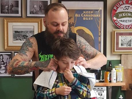 Nằm lăn ra đất để cắt tóc cho cậu bé, hành động này của người thợ đã được cả thế giới tung hô - ảnh 1