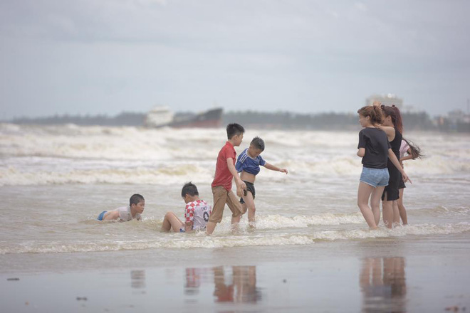 Chùm ảnh: Bất chấp sóng to gió lớn sau bão số 2, nhiều gia đình vẫn đưa trẻ em ra tắm biển Cửa Lò - Ảnh 7.