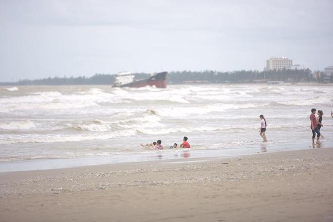 Chùm ảnh: Bất chấp sóng to gió lớn sau bão số 2, nhiều gia đình vẫn đưa trẻ em ra tắm biển Cửa Lò - Ảnh 8.
