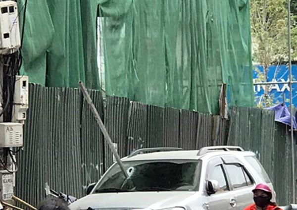 Hà Nội: Đang đỗ ven đường, ô tô 7 chỗ bị thanh thép dài 3m rơi thủng kính lái - Ảnh 1.