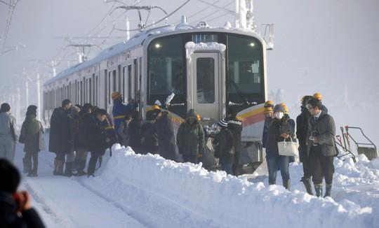 Nhật Bản: Tuyết chôn chân xe lửa, khách rã rời đứng cả đêm - Ảnh 1.