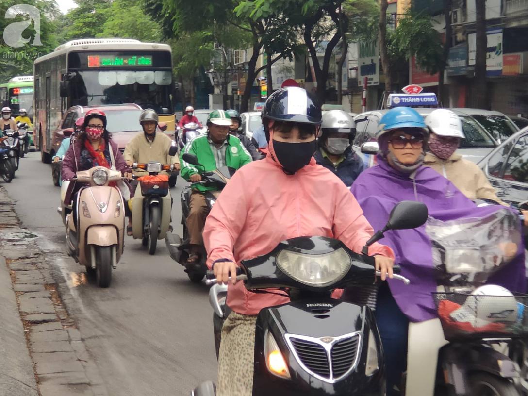 Hà Nội: Không khí lạnh tràn về, nhiệt độ giảm mạnh, người dân thích thú mặc áo ấm ra đường dưới trời mưa phùn - Ảnh 2.