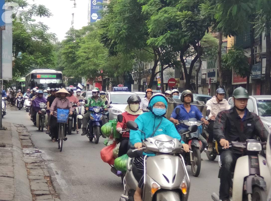 Hà Nội: Không khí lạnh tràn về, nhiệt độ giảm mạnh, người dân thích thú mặc áo ấm ra đường dưới trời mưa phùn - Ảnh 3.