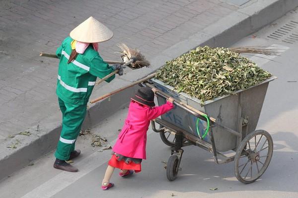 Cô bé giúp mẹ là công nhân vệ sinh đẩy xe rác ngày mùng 2 Tết khiến MXH ấm lòng và sự thật đằng sau - Ảnh 1.