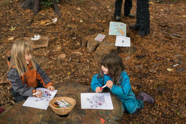Stelyn Carter, 5 tuổi và Alma Essers, 3 tuổi dùng gốc cây làm bàn học.