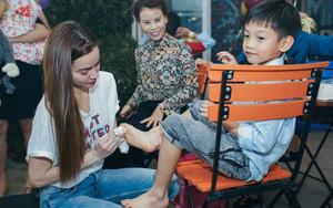 Hồ Ngọc Hà cúi người lau chân cho con trai trong tiệc sinh nhật lên 7 tuổi
