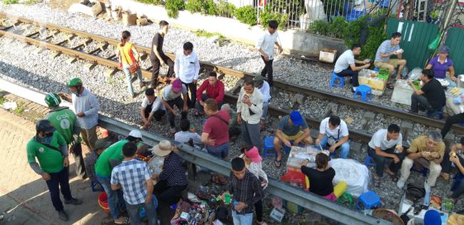 Hà Nội: Bệnh nhân bất chấp tính mạng ngồi ăn vặt, trà đá ngay trên đường tàu trước cổng bệnh viện  - Ảnh 2.