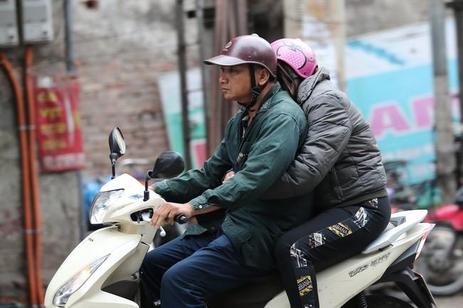 Hà Nội: Không khí lạnh tràn về, nhiệt độ giảm mạnh, người dân co ro, mặc áo ấm khi ra đường - Ảnh 1.