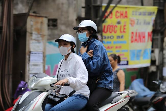 Hà Nội: Không khí lạnh tràn về, nhiệt độ giảm mạnh, người dân co ro, mặc áo ấm khi ra đường - Ảnh 2.