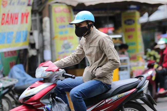 Hà Nội: Không khí lạnh tràn về, nhiệt độ giảm mạnh, người dân co ro, mặc áo ấm khi ra đường - Ảnh 4.