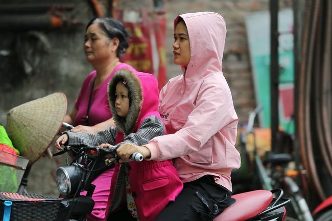 Hà Nội: Không khí lạnh tràn về, nhiệt độ giảm mạnh, người dân co ro, mặc áo ấm khi ra đường - Ảnh 12.