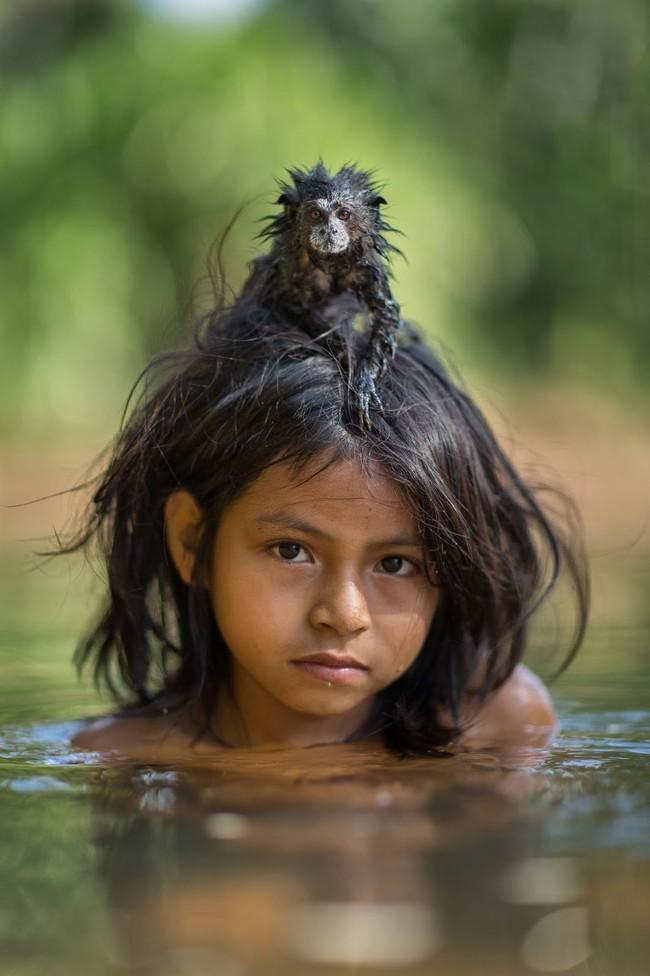 Câu chuyện xúc động và sự thật tàn khốc ít ai biết về em bé 11 tuổi mồ côi sống cùng chú khỉ con trong rừng sâu - Ảnh 1.