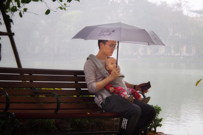 Địu con trước ngực dạo bờ hồ ngày mưa bụi, sắc mặt an tĩnh của bố bỉm sữa mới là thứ gây chú ý - Ảnh 1.