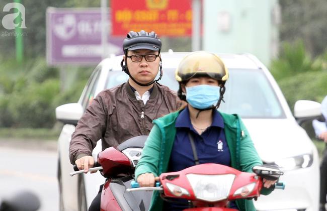 Hà Nội: Gió lạnh bất ngờ xuất hiện khiến nhiệt độ giảm mạnh, người dân quàng khăn, mặc áo rét ra đường - Ảnh 4.
