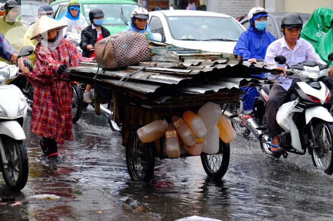 Nước ngập đến bàn thờ ông thần Tài sau mưa lớn ở TP.HCM: Người bì bõm tát nước, người bán buôn ế ẩm - Ảnh 11.