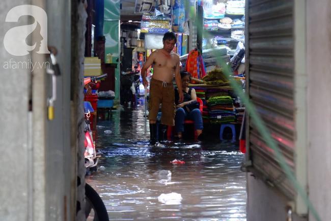 Nước ngập đến bàn thờ ông thần Tài sau mưa lớn ở TP.HCM: Người bì bõm tát nước, người bán buôn ế ẩm - Ảnh 14.