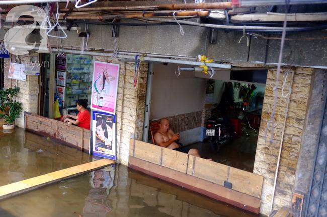 Nước ngập đến bàn thờ ông thần Tài sau mưa lớn ở TP.HCM: Người bì bõm tát nước, người bán buôn ế ẩm - Ảnh 16.