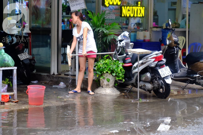 Nước ngập đến bàn thờ ông thần Tài sau mưa lớn ở TP.HCM: Người bì bõm tát nước, người bán buôn ế ẩm - Ảnh 7.