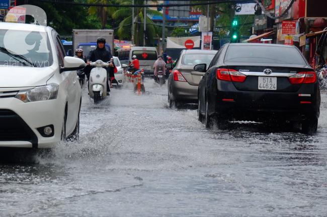 Nước ngập đến bàn thờ ông thần Tài sau mưa lớn ở TP.HCM: Người bì bõm tát nước, người bán buôn ế ẩm - Ảnh 1.