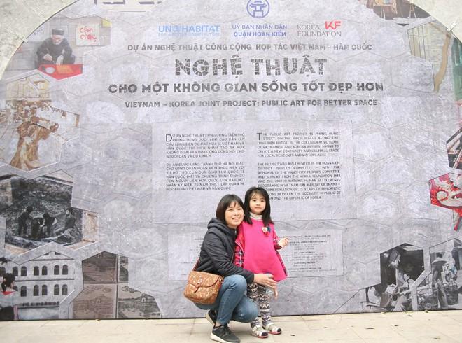 Người Hà Nội xúng xính áo dài Tết chụp ảnh trước cổng vòm phố Phùng Hưng - Ảnh 1.