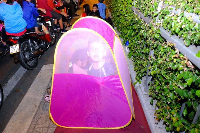 Bố mẹ đem cả mùng mền, trải chiếu ru con ngủ để chờ xem bắn pháo hoa mừng năm mới - ảnh 1