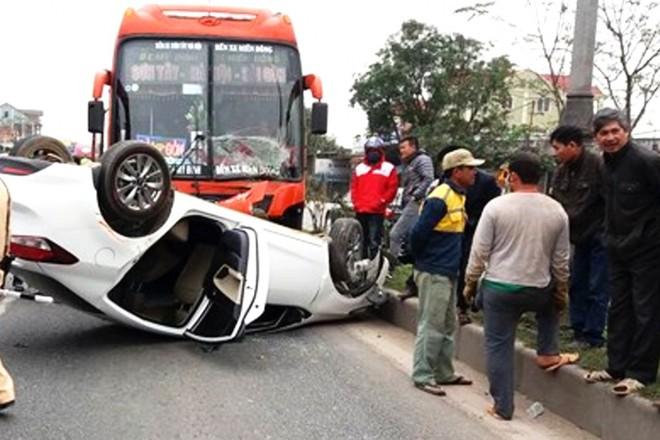 Xe khách tông xe con lật ngửa trên quốc lộ, 3 nạn nhân mắc kẹt bên trong - Ảnh 1.