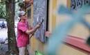 Người đàn ông Mỹ cầm dao, chổi tỉ mẩn gỡ từng mẩu quảng cáo, rao vặt trên tường Hà Nội