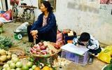Bức ảnh con trai cặm cụi viết bài bên hàng trái cây mưu sinh của mẹ khiến chúng ta nhận ra hạnh phúc là gì