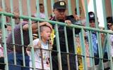 Bé trai khóc nức nở khi bị kẹt cổ giữa hai song sắt tại sân vận động