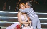 Mỹ Tâm ngồi sụp xuống sân khấu để một fan nhí ôm chặt và hôn má