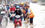 Sài Gòn ngập cả buổi sáng sau trận mưa đêm, nhân viên thoát nước ra đường đẩy xe chết máy giúp người dân