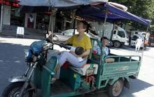 Vừa lái xe vừa cho con bú, lại chở thêm bé nữa đằng sau, mẹ trẻ gây tranh cãi dữ dội