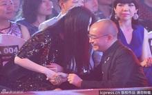Băng Phạm nắm tay thì thầm với một người đàn ông trước đám đông