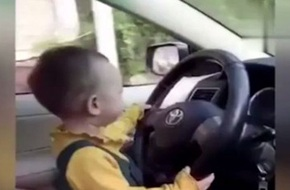 Con 1 tuổi ngồi trên đùi bố lái xe ô tô, mẹ ngồi bên cười thích thú gây tranh cãi