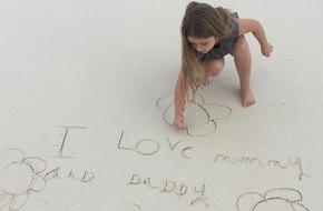 Harper cặm cụi viết lời nhắn yêu thương trên cát cho bố mẹ