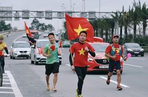 Chùm ảnh: Người hâm mộ cầm cờ Tổ quốc, chạy bộ ra sân bay Nội Bài để đón U23 Việt Nam