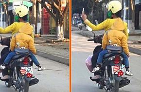 Bà mẹ chở hai con trên xe máy vẫn vô tư chụp ảnh tự sướng