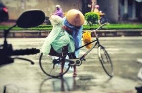 Mẹ dừng xe đạp che chắn cẩn thận cho con giữa trời mưa to