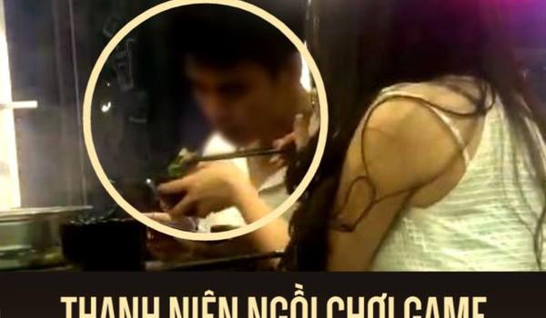 Thanh niên ngồi chơi game được bạn gái bón cho ăn