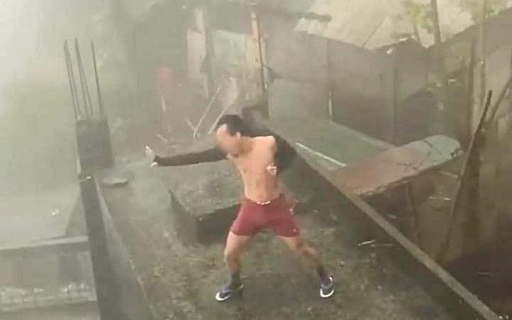 Xôn xao clip người đàn ông cởi trần đi dép tông gồng mình múa may trên nóc nhà giữa trời mưa bão