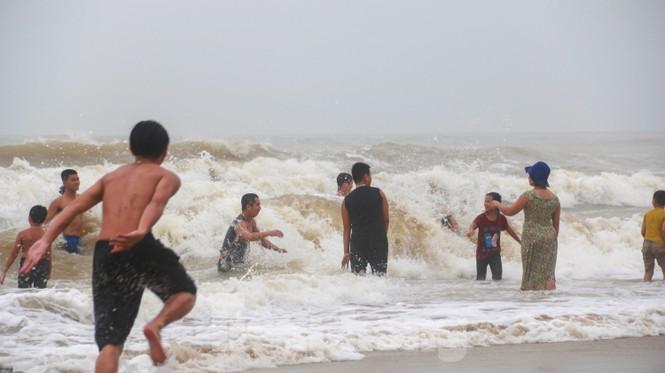 Biển động sóng cao phủ đầu, người dân Đà Nẵng vẫn liều mình tắm biển sau bão - Ảnh 1.