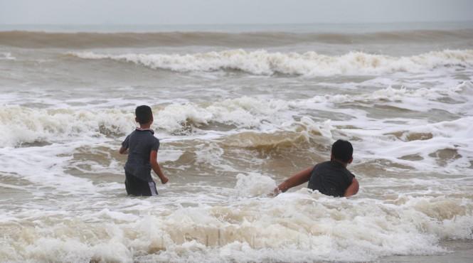 Biển động sóng cao phủ đầu, người dân Đà Nẵng vẫn liều mình tắm biển sau bão - Ảnh 6.