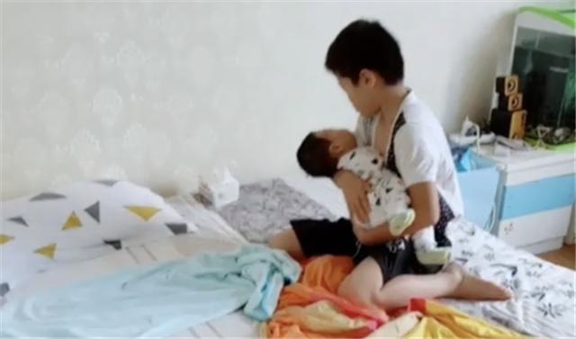 """Nhìn hành động bế ru, đặt em bé ngủ vô cùng """"thần sầu"""" của cậu bé này, nhiều bà mẹ trẻ có khi còn hổ thẹn không bằng! - Ảnh 1."""