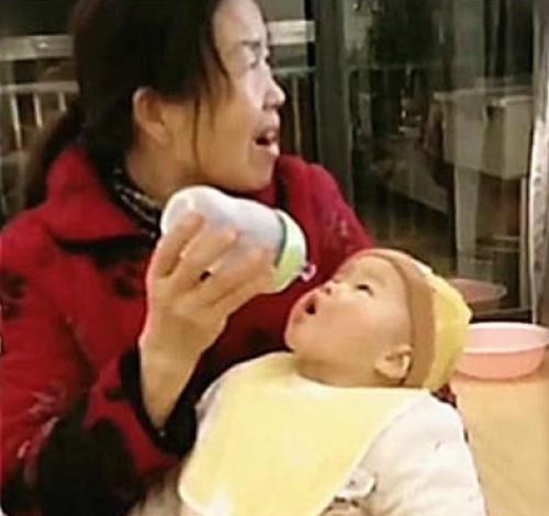 """Bà cho cháu bú bình nhưng lại bị chiếc tivi """"mê hoặc"""", hình ảnh em bé há miệng chờ sữa trong """"bất lực"""" khiến người xem không nhịn được cười vì quá đáng yêu - Ảnh 2."""