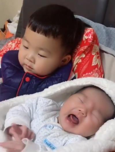 Em gái đang khóc ngằn ngặt đòi mẹ, anh trai 2 tuổi đã nhanh trí nghĩ ra cách dỗ em nín khóc hiệu quả tức thì - Ảnh 1.