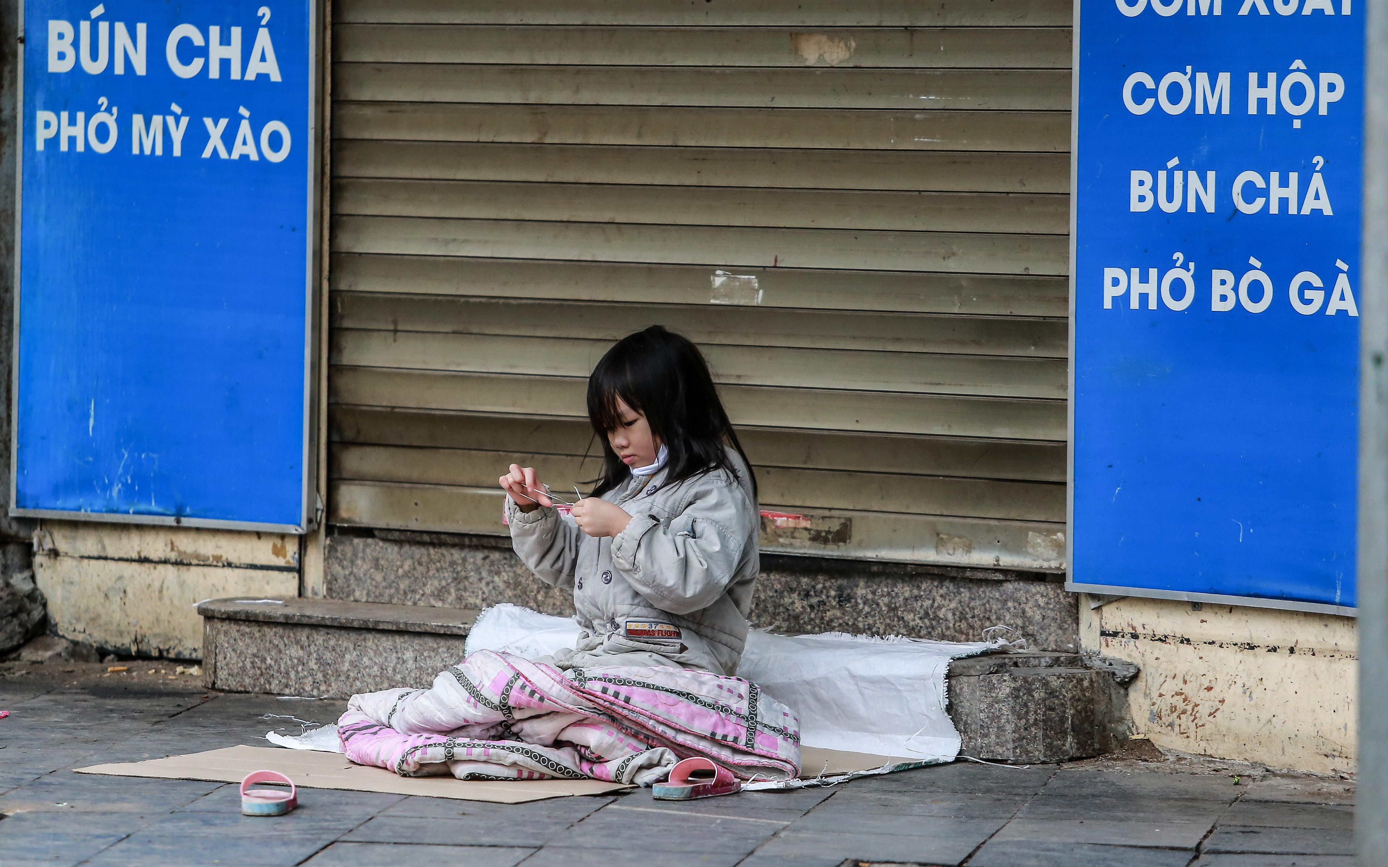 Những ngày Hà Nội vắng vẻ bởi cách ly xã hội, đâu đó nơi góc phố cổ là hình ảnh bé gái lủi thủi trên tấm bìa giấy giữa trời mưa phùn giá rét