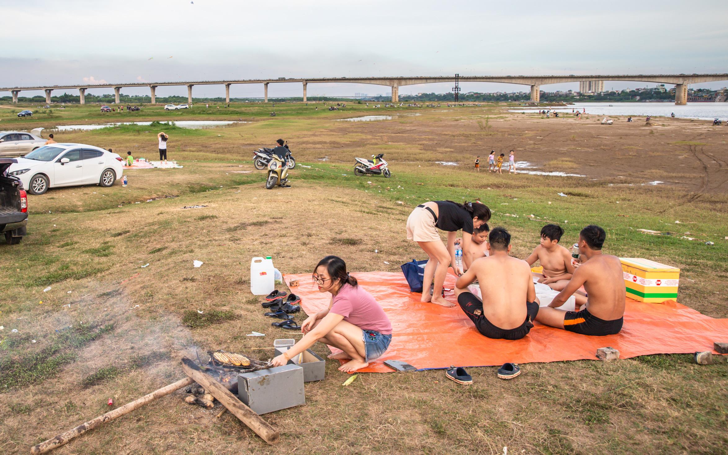 Rời xa ồn ào nơi phố thị, nhiều gia đình tìm đến bãi bồi dưới chân cầu Vĩnh Tuy để sống ''chill'', thoả sức bắt ốc, nướng cá sống lại một thời tuổi thơ
